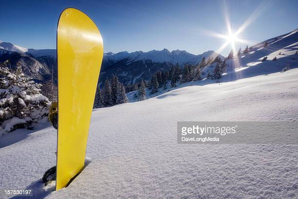 Yellow snowboard in snow on mountain