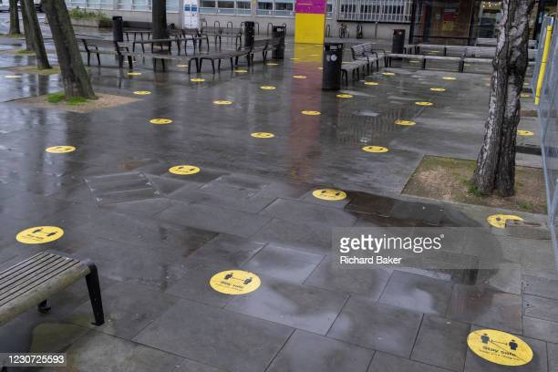 Yellow social distancing stickers remain on the pavement outside the London College of Cummincation during the third lockdown of the Coronavirus...