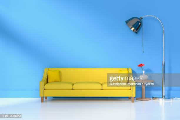 yellow sofa against blue wall at home - ソファ ストックフォトと画像