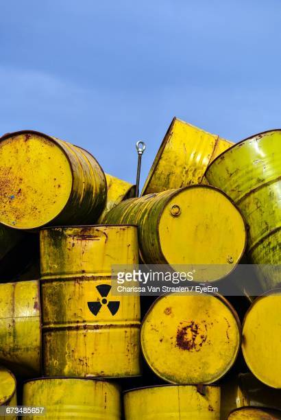 Yellow Stacked Oil Drums Against Sky