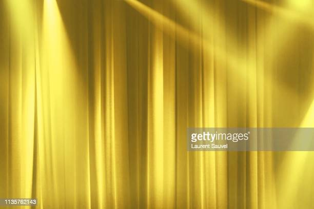 yellow stage curtain in the spotlights with light rays - stage curtain stock pictures, royalty-free photos & images