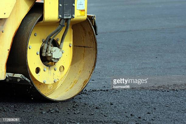Yellow steamroller working on the street