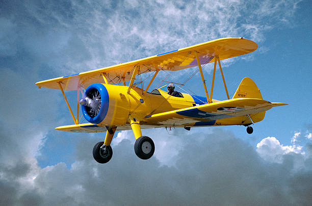 Yellow Stearman 5YP bi-plane flying in cloudy sky