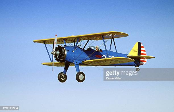 yellow stearman 9046v bi-plane flying in blue sky - 1943 stock pictures, royalty-free photos & images
