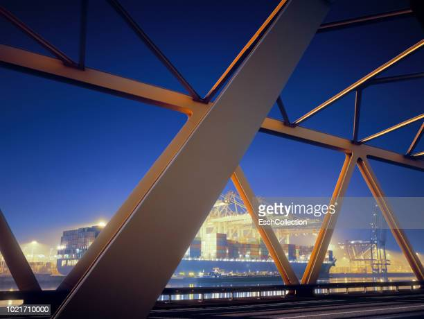 Yellow steel bridge and container terminal at dawn