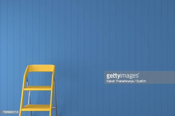 yellow step ladder against blue wall - step ladder stock photos and pictures