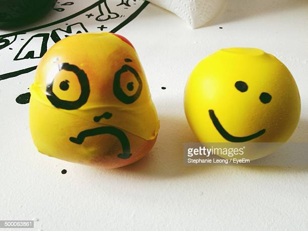 Yellow stress balls with sad and happy faces on table
