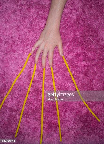 Yellow String Emerging From Fingers on Pink Rug