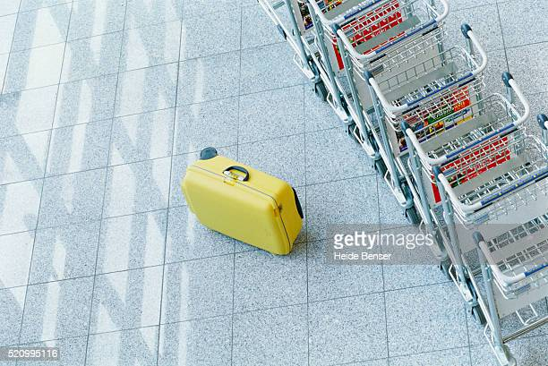 Yellow suitcase and luggage trollies