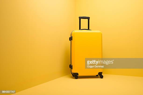 Yellow suitcase standing on yellow background