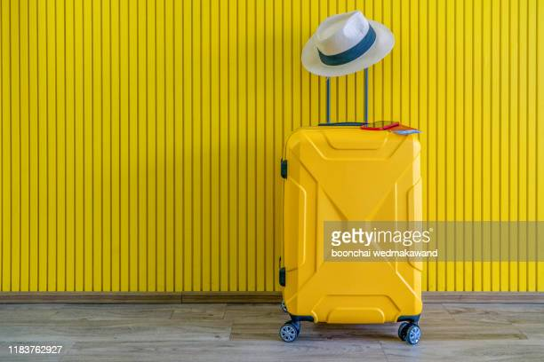 yellow suitcase with sun glasses and hat on yellow background. travel concept. minimal style - suitcase stock pictures, royalty-free photos & images
