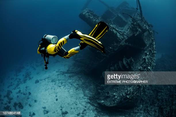 yellow suited scuba diver exploring an overgrown shipwreck under the red sea - sunken stock pictures, royalty-free photos & images