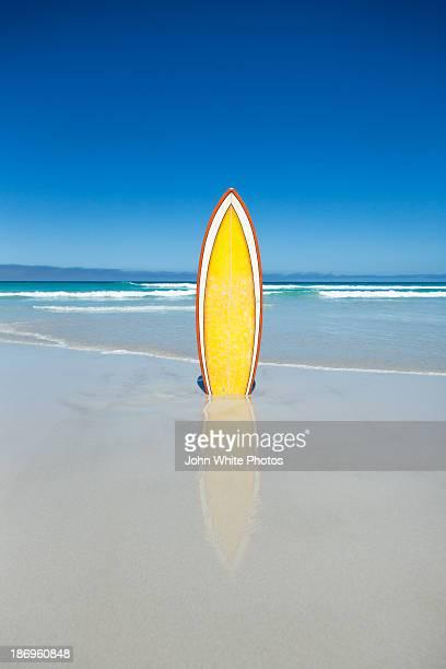 Yellow surfboard on a beach.
