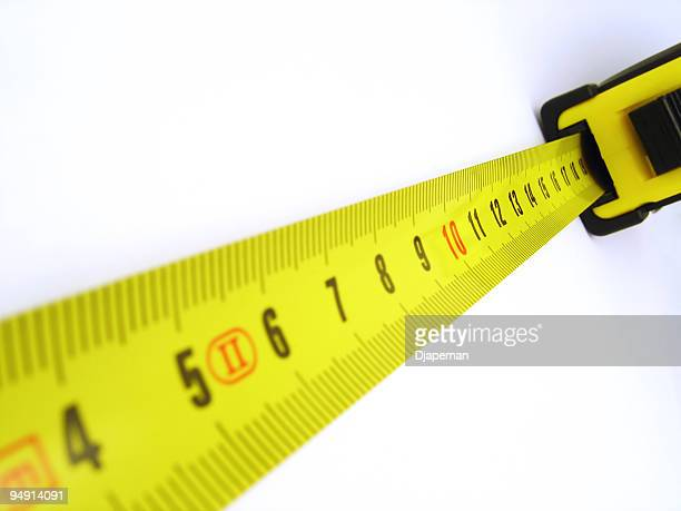 Yellow tape measure outstretched on a white wall