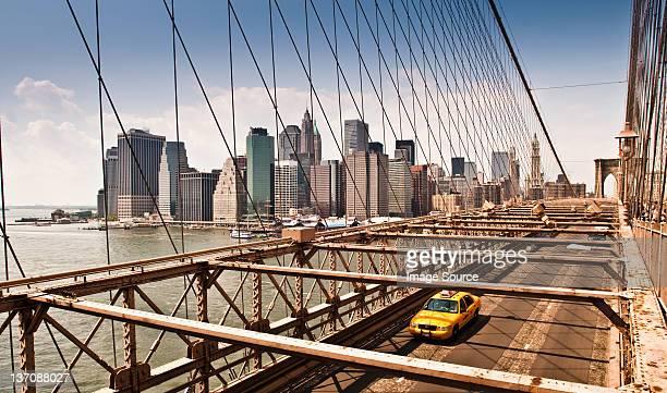 yellow taxi cab crossing manhattan bridge, manhattan, new york, usa - yellow taxi stock pictures, royalty-free photos & images