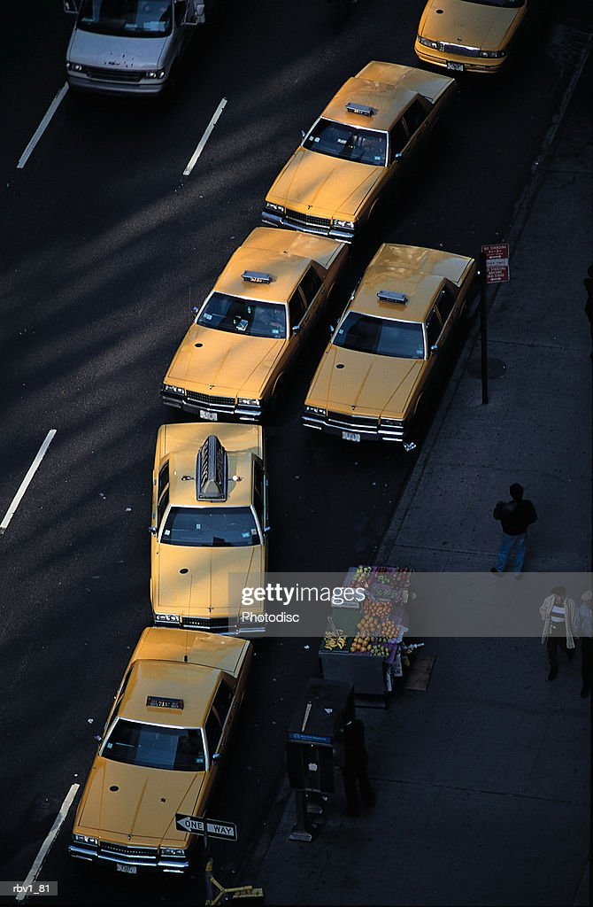 Yellow taxi cabs line the edge of a street as people pass newspaper stands on a sidewalk : Foto de stock