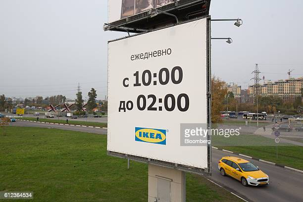 A yellow taxi passes a large sign advertising store opening times outside the Ikea AB retail store in Khimki Russia on Monday Oct 3 2016 Ikea's...