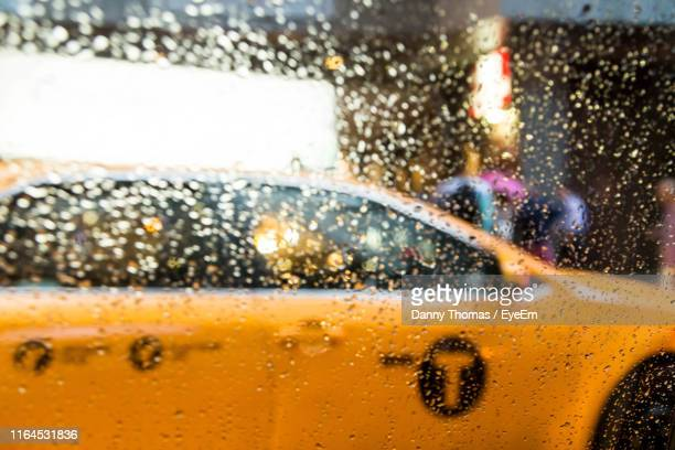 Yellow Taxi Seen Through Wet Glass Window During Monsoon