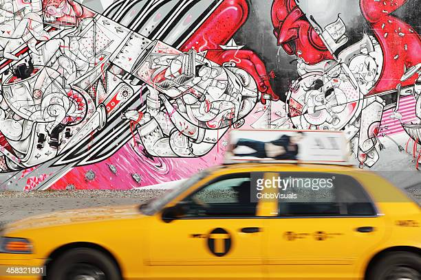 NYC yellow taxi speeds past How Nosm street art mural