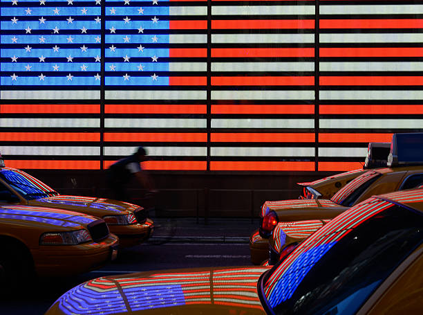 Yellow taxis at Time Square, American flag in background