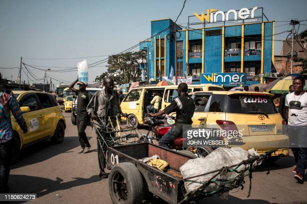 Yellow taxis clog up the streets of Kinshasa, capital of Democratic Republic of Congo on June 10, 2019. - Cities almost everywhere have transport...