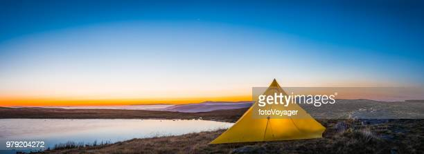 Yellow tent camping in mountain wilderness beside sunrise lake panorama