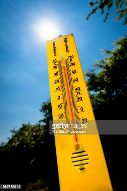 a yellow thermometer against a bright sunlit sky - wetter stock-fotos und bilder