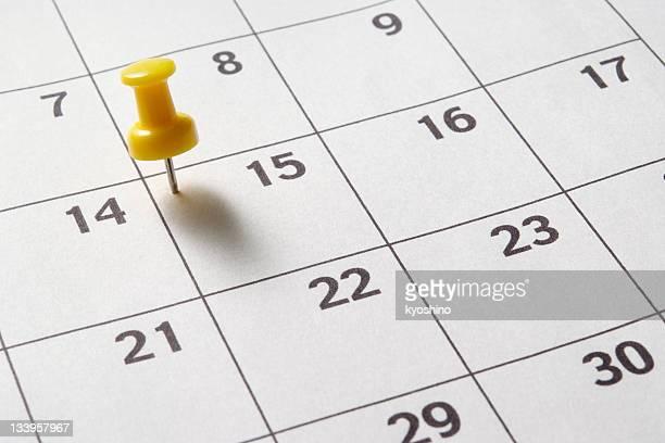 Yellow thumbtack in calendar with shadow