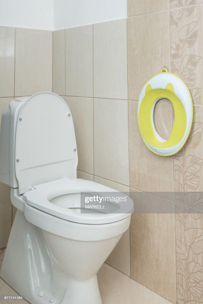 Yellow Toilet Seat For Small Kids Next To The Stock Photo