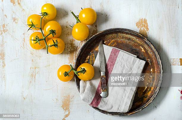 Yellow tomatoes with a knife on a wooden board