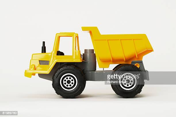 yellow toy articulated dump truck - dump truck stock pictures, royalty-free photos & images