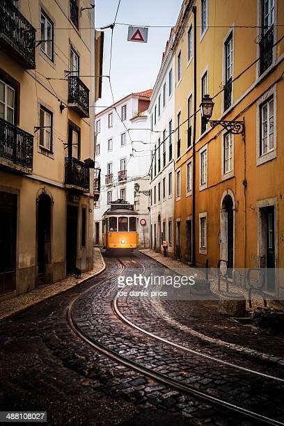 yellow tram, alfama district - alfama stock photos and pictures
