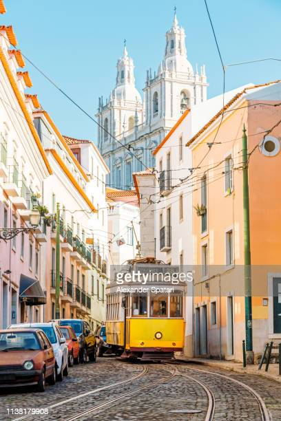 yellow tram on the narrow street of alfama district in lisbon, portugal - tram stockfoto's en -beelden
