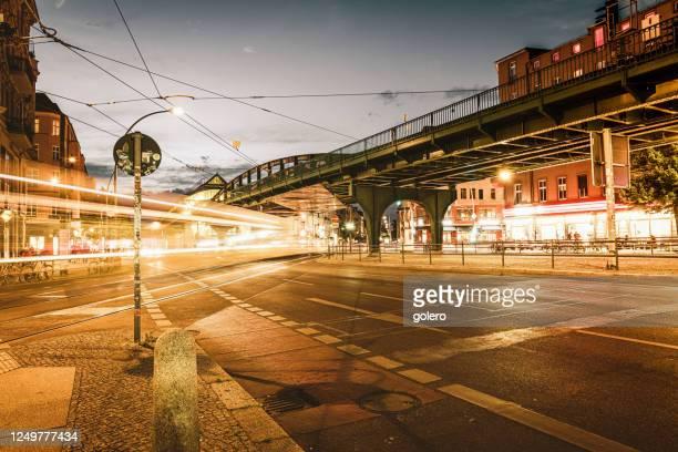 夕暮れ時のプレンツラウアーベルクの地下鉄ブリッジの下を通過する黄色いトラム、ベルリン - プレンツラウアーベルグ ストックフォトと画像