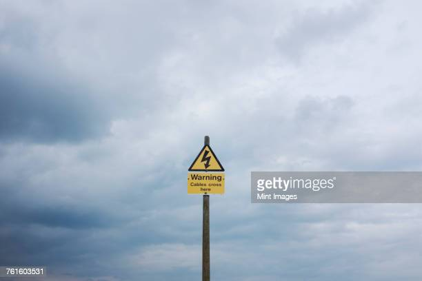 yellow triangular warning sign on pole against cloudy sky. - warning sign stock pictures, royalty-free photos & images