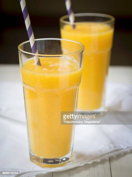 Yellow tropic fruit smothie in two tall glasses.