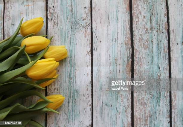 Yellow tulips on rustic wooden table