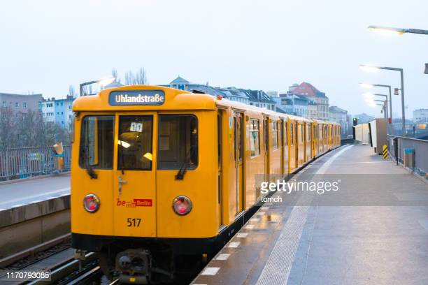 a yellow u-bahn car arriving to the station in berlin, germany - u bahn stock pictures, royalty-free photos & images
