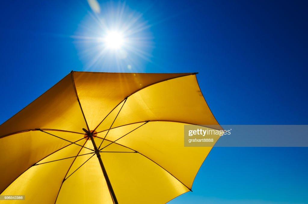 Yellow Umbrella With Bright Sun And Blue Sky : Stock Photo