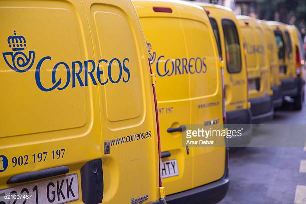 Yellow vans of the Spanish mail company of Correos in the city of Barcelona Catalonia Europe