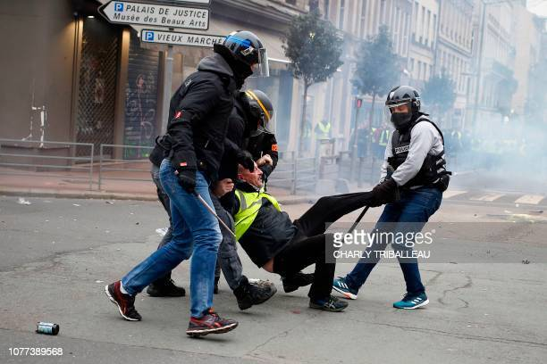 TOPSHOT A Yellow Vest antigovernment protester is detained by security personnel in Rouen northwestern France on January 5 during a nationwide day of...