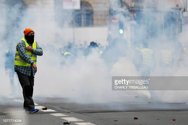 A Yellow Vest antigovernment protester makes a quenelle sign as teargas clouds surround him during clashes with security personnel on a street in...