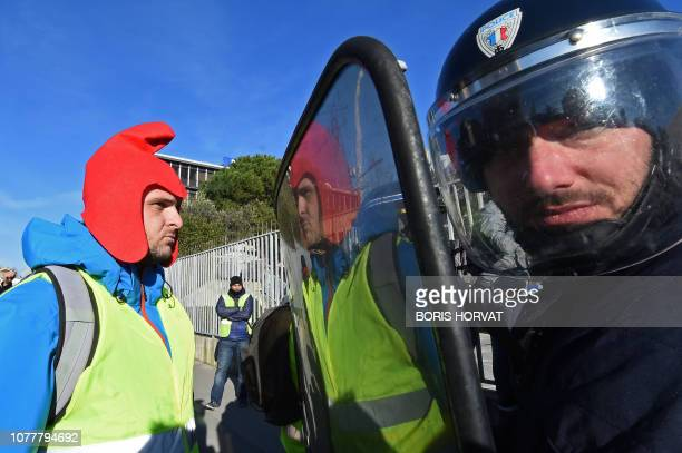 """Yellow vest demonstrator faces riot police officers in Marseille, southern France, on January 5 during a rally by yellow vest """"Gilets Jaunes""""..."""