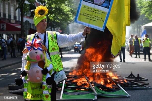 A yellow vest demonstrator stands in front of a fire as they gather in the Bercy neighborhood to protest for a 23rd week on April 20 2019 in Paris...