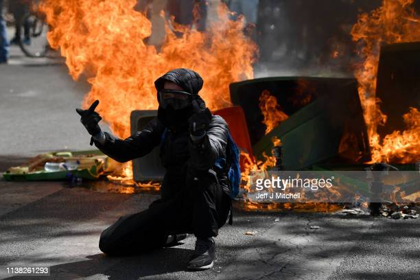 Yellow vest demonstrators gstand in front of a fire in the Bercy neighborhood as they protest for a 23rd week on April 20 2019 in Paris France Over...