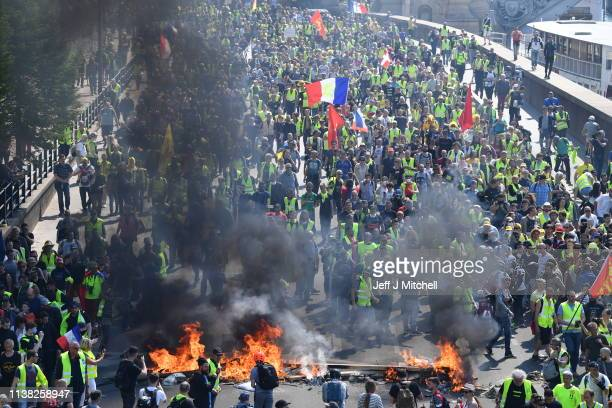 Yellow vest demonstrators light a fire as they gather in the Bercy neighborhood to protest for a 23rd week on April 20 2019 in Paris France Over One...