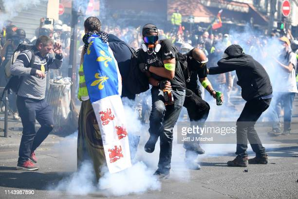 A yellow vest demonstrators walk through smoke in the Bercy neighborhood as they protest for a 23rd week on April 20 2019 in Paris France Over One...
