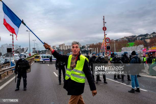 A yellow vest Gilet Jaune protestor holds a French flag as he walks in front of police officers during an antigovernment demonstration in Lyon on...