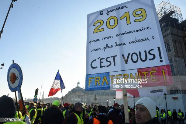 A yellow vest Gilet Jaune protestor holds a sign reading January 5 2019 for my birthday the nicest present is you Fraternity as he takes part in an...