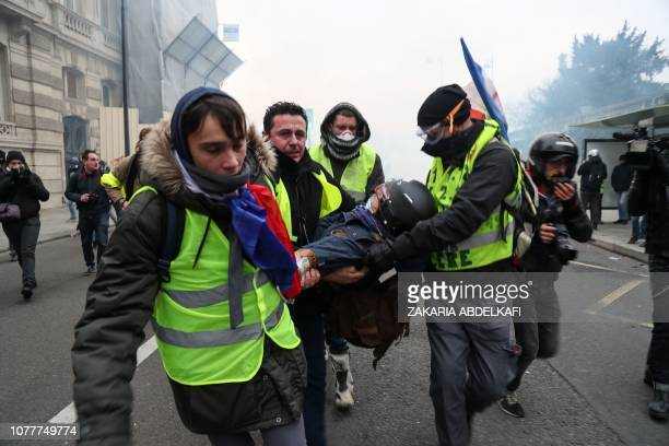 Yellow vest Gilets Jaunes antigovernment protestors attend to a photographer who was injured during clashes with security personnel at a rally in...